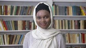 encanto : Young charming african muslim girl in hijab is watching at camera, religioun concept, booksheves on background