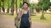 kazak : Young asian female student with tattoo standing with backpack and looking in camera in park near university, confident