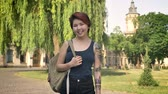 kazak : Young asian women with tattoo standing and looking in camera near university in park, student holding backpack, smiling
