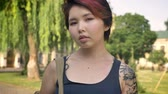 kazak : Portrait of young asian female student with tattoo standing with backpack and looking in camera in park near university, confident