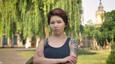 kazak : Portrait of young asian women with tattoo crossing hands and looking into camera in park near university, serious and concerned