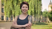kazak : Asian young tattooed female student standing in park near university and looking in camera, smiling and cheerful