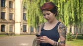 kazak : Asian beautiful young women with tattoo standing and holding phone in park near university, student texting on phone