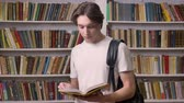 knihovna : Young beautiful man in white shirt standing in library and reading, looking at camera and holding book, bookshelves background, serious