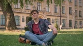 maço : Young handsome man is sitting on lawn in park, listening music with earphones, relax concept, building on background