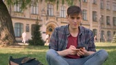 tapping : Young handsome man is sitting on grass in park, tapping on smartphone, wayching at camera, relax concept, communication concept, building on background
