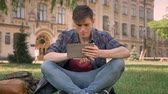 tomb : Young man is sitting on grass in park, watching pages in Internet on tablet, watching at camera, relax concept, communication concept, building on background