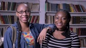 prateleira de livros : Two young african american female friends standing in library and smiling at camera, bookshelves background, happy
