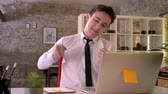 sião : Young businessman is working with laptop in office, happy because of business victory, keeping hand fist, gesture concept, communication concept