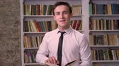 читатель : Young businessman is searching information in book in library, watching at camera, relax concept