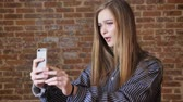 varredura : Young beautiful girl is making video on her smartphone, speaking, communication concept, brick background Stock Footage