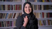 pakisztán : Young beautiful muslim girl in hijab puts on bag, watching at camera, smiling, bookshelf on background, religious concept