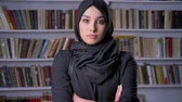 islamite : Young beautiful muslim girl in hijab crosses arms, watching at camera, religious concept, bookshelf on background Stock Footage
