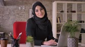 islamite : Young beautiful muslim girl in hijab is working with laptop in office, watching at camera, smiling, work concept, business concept, communication concept, religious concept