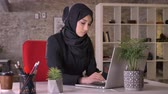 islamite : Young muslim girl in hijab is working with laptop in office, watching at camera, smiling, work concept, business concept, communication concept, religious concept Stock Footage