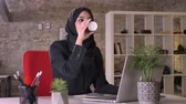 pakistan : Young muslim girl in hijab is working with laptop in office, drinking coffe, work concept, business concept, communication concept, religious concept