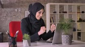 islamite : Young muslim girl in hijab is working with laptop in office, happy because of good news, work concept, business concept, communication concept, religious concept Stock Footage