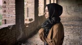 immigrant : Young beautiful muslim woman in black hijab standing in abandoned building and looking at camera with scared and terrified expression