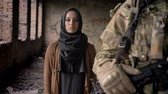 radical : Young muslim woman in hijab standing behind armed soldier with weapon and looking at camera with sad look, war concept