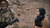 radical : Armed caucasian soldier with weapon and muslim woman in hijab standing near brick wall, woman looking at man with gun, war concept