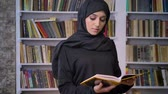 islamite : Young sweet muslim girl in hijab opens book, reads, religious concept, bookshelf on background