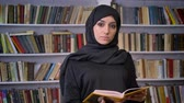 literatura : Young serious muslim girl in hijab is reading book, watching at camera, religious concept, bookshelf on background