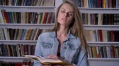 книги : Young serious woman is reading book in library, watching at camera, bookshelf on backgorund