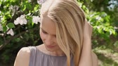 memnun : Young cute blond girl is watching at camera in park in daytime in summer, smiling, touchig hair Stok Video