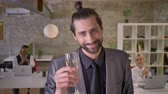 colegas de trabalho : Happy businessman with beard is standing and holding glass of champagne in office, colleagues are clapping, company party concept Vídeos