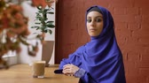 konsantre : Young muslim woman in hijab sitting in cafe and looking at camera, serious beautiful female in headscarf Stok Video