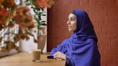 perfurante : Young muslim woman in hijab turning head and smiling at camera, sitting in cafe, female with pierced nose