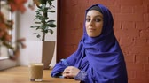 perfurante : Beautiful young muslim woman in blue hijab turning and smiling at camera, sitting in cafe, lady with pierced nose Stock Footage