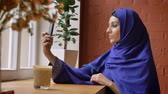 hijab : Young muslim woman in blue hijab taking selfie and sitting in cafe, beautiful female with pierced nose