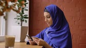 perfurante : Beautiful young muslim woman in blue hijab rewriting info from card to her phone, sitting in modern cafe