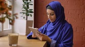perfurante : Young beautiful muslim woman in blue hijab using tablet and sitting in cafe, charming female with pierced nose Stock Footage