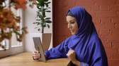 nacionalidade : Young happy muslim woman in blue hijab having video chat through tablet, sitting in modern cafe, smiling Stock Footage