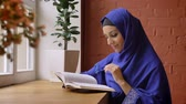 knihovna : Young beautiful woman in blue hijab reading book and sitting in cafe, charming lady with pierced nose
