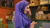 islamite : Young beautiful muslim woman in hijab sitting in cafe and typing on phone, smiling