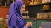 islamite : Young charming muslim woman in hijab turning and smiling at camera, sitting in cafe, happy and cheerful