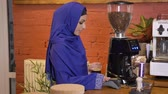 islamite : Young muslim woman in hijab holding drink and making card payment in cafe, smiling Stock Footage