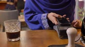islamite : Young muslim woman in hijab making contactless payment by smartphone and taking her coffee, smiling