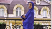 varanda : Young beautiful muslim woman in hijab standing on balcony, turning and smiling at camera, building in background