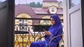 islamite : Young charming muslim woman in hijab sitting in chair on balcony and typing on cell phone
