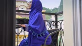 varanda : Young muslim woman in hijab going and sitting in chair on balcony, charming female relaxing