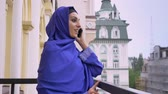 islamite : Young beautiful muslim woman in hijab standing on balcony and talking on phone during rain