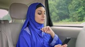 peçe : Young muslim woman in hijab in car on passenger rear seat and typing on cell phone Stok Video