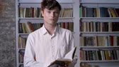учебник : Serious brunette man is reading book, watching at camera, library on background