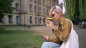 perfurante : Young blonde woman in glasses drinking coffee and texting on phone, sitting in park near university