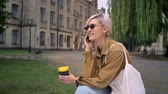 perfurante : Trendy pretty woman in sunglasses holding coffee and talking on phone, sitting in park near university