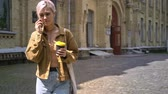 perfurante : Young blonde woman with short haircut walking near university, talking on phone and holding coffee Stock Footage